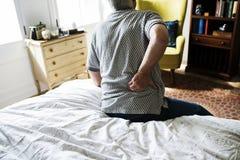 Homme supérieur s'asseyant sur le lit en douleur Photographie stock libre de droits