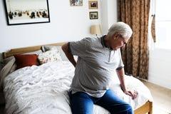 Homme supérieur s'asseyant sur le lit en douleur Image libre de droits
