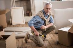 Homme supérieur s'asseyant sur le plancher avec le marteau à disposition à la nouvelle maison Images stock