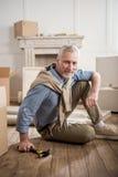 Homme supérieur s'asseyant sur le plancher avec le marteau à disposition à la nouvelle maison Photographie stock libre de droits