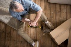 Homme supérieur s'asseyant sur le plancher avec le marteau à la nouvelle maison Images libres de droits
