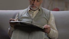 Homme supérieur s'asseyant sur le sofa à la maison, lisant les dernières nouvelles quotidiennes dans des médias d'impression banque de vidéos