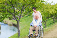 Homme supérieur s'asseyant sur un fauteuil roulant avec le travailleur social Image stock