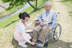 Homme supérieur s'asseyant sur un fauteuil roulant avec le travailleur social Photos stock