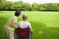 Homme supérieur s'asseyant sur un fauteuil roulant avec son épouse Photos stock