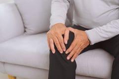 Homme supérieur s'asseyant sur un sofa dans le salon à la maison et touchant son genou par la douleur photos libres de droits