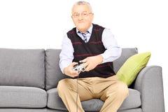 Homme supérieur s'asseyant sur un sofa et jouant le jeu vidéo Photographie stock