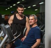Homme supérieur s'exerçant avec l'entraîneur dans le gymnase Images stock