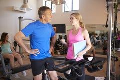 Homme supérieur s'exerçant sur la machine de recyclage encouragé par l'entraîneur personnel féminin In Gym photos stock