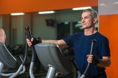 Homme supérieur s'exerçant sur la machine elliptique dans le gymnase Photographie stock libre de droits