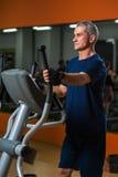 Homme supérieur s'exerçant sur la machine elliptique dans le gymnase Photographie stock