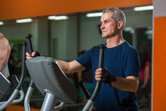 Homme supérieur s'exerçant sur la machine elliptique dans le gymnase Photos libres de droits