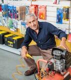 Homme supérieur sûr avec le compresseur d'air dans le magasin Image stock
