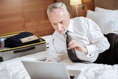 Homme supérieur satisfaisant regardant fixement l'écran Image stock