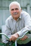 Homme supérieur se penchant sur le guidon de sa bicyclette Image stock