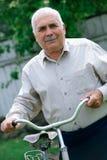 Homme supérieur se penchant sur le guidon de sa bicyclette Photo libre de droits