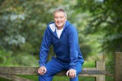 Homme supérieur se reposant sur la porte pendant l'exercice dans la campagne Photo stock