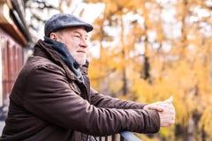 Homme supérieur se reposant sur une terrasse en nature d'automne Images libres de droits