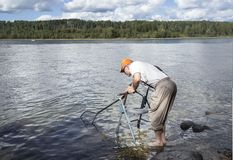 Homme supérieur se tenant au bord d'un lac avec son marcheur et filet de pêche Images stock