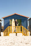 Homme supérieur se tenant avec la planche de surf à la hutte de plage Image libre de droits