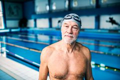 Homme supérieur se tenant dans une piscine d'intérieur Photo stock