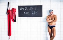 Homme supérieur se tenant dans une piscine d'intérieur Photo libre de droits