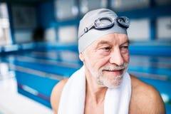 Homme supérieur se tenant dans une piscine d'intérieur Photographie stock libre de droits