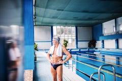Homme supérieur se tenant prêt la piscine d'intérieur Image stock