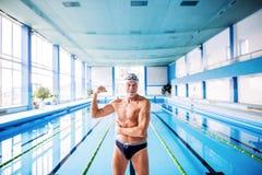 Homme supérieur se tenant prêt la piscine d'intérieur Images libres de droits