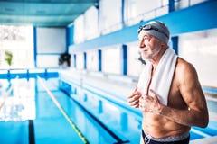 Homme supérieur se tenant prêt la piscine d'intérieur Photo stock