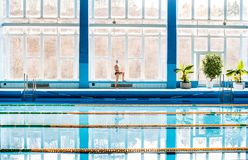 Homme supérieur se tenant prêt la piscine d'intérieur Photo libre de droits