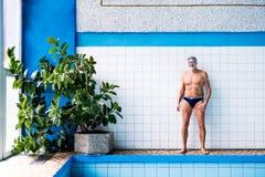 Homme supérieur se tenant prêt la piscine d'intérieur Images stock