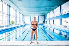 Homme supérieur se tenant prêt la piscine d'intérieur Photographie stock