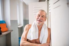 Homme supérieur se tenant prêt les casiers dans une piscine d'intérieur Photos stock
