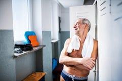 Homme supérieur se tenant prêt les casiers dans une piscine d'intérieur Photographie stock libre de droits