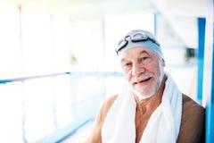 Homme supérieur se tenant prêt une piscine d'intérieur Images stock