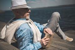 Homme supérieur se trouvant avec le livre et regardant loin sur le quai Images stock
