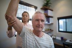 Homme supérieur semblant parti tandis que coude de examen de docteur féminin Photos libres de droits