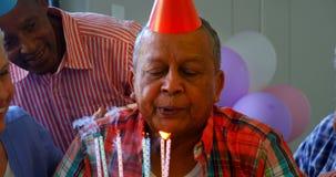 Homme supérieur soufflant les bougies sur un gâteau d'anniversaire avec ses amis 4k banque de vidéos