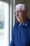 Homme supérieur souffrant de la dépression regardant hors de la fenêtre Images stock