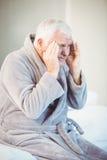 Homme supérieur souffrant du mal de tête tout en se reposant sur le lit Photos stock