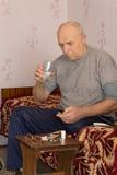 Homme supérieur souffrant prenant le médicament image stock