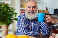 Homme supérieur souriant tenant la tasse de thé dans des mains tout en se penchant sur t Photo stock