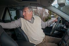 Homme supérieur soutenant dans la voiture images stock