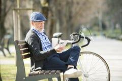 Homme supérieur sur le banc avec la bicyclette et le smartphone, textotant Images stock