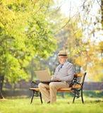 Homme supérieur sur le banc et travailler sur un ordinateur portable en parc Images stock