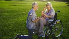 Homme supérieur sur le genou proposant la femme sur le fauteuil roulant banque de vidéos