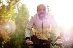 Homme supérieur sur le tour de cycle dans la campagne Images stock