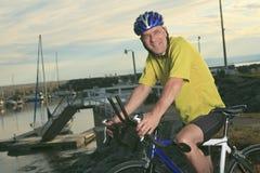 Homme supérieur sur le vélo au coucher du soleil Photos stock
