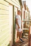 Homme supérieur tenant la bouteille tout en se tenant à la hutte de plage Image libre de droits